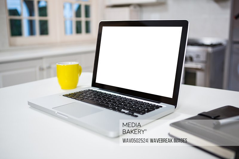 Laptop with personal organizer and coffee mug on the table in the kitchen at home
