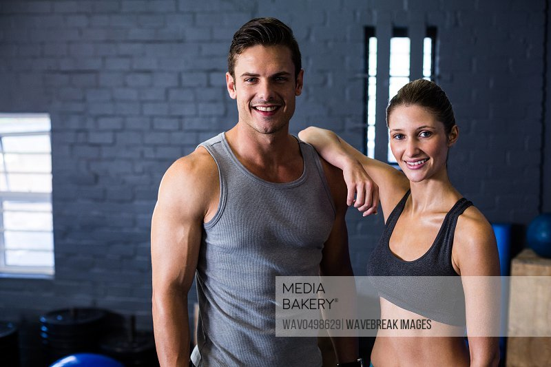 Portrait of happy male and female athlete standing against wall in gym