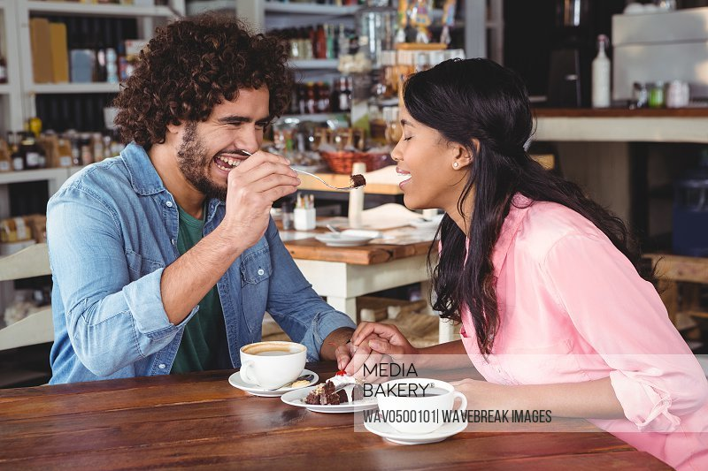 Man feeding dessert to woman in cafeteria
