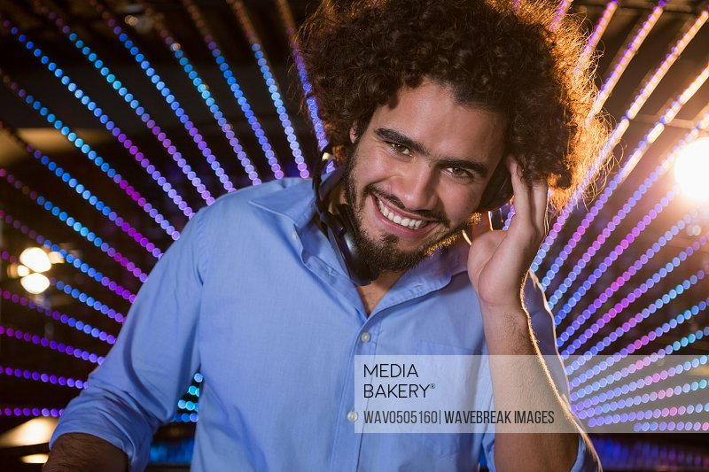Portrait of male DJ playing music at the nightclub