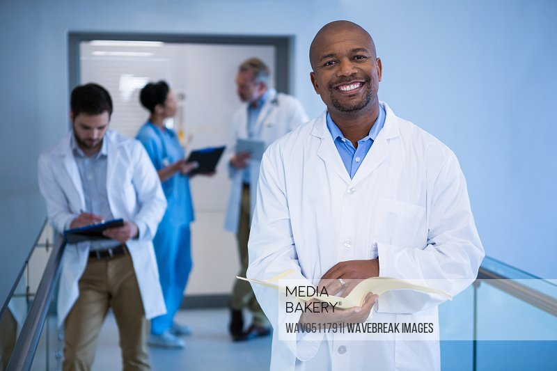 Portrait of male doctor holding file in corridor at hospital