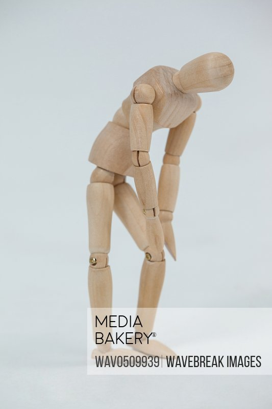 Injured wooden figurine standing with hands on knee against white background