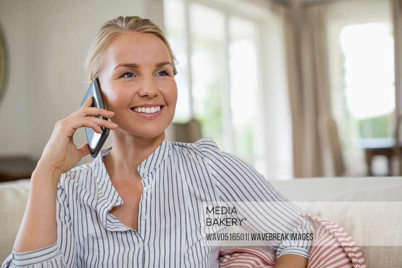 Smiling woman talking on mobile phone in living room