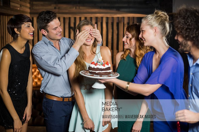 Group of friends surprising a woman with birthday cake in bar