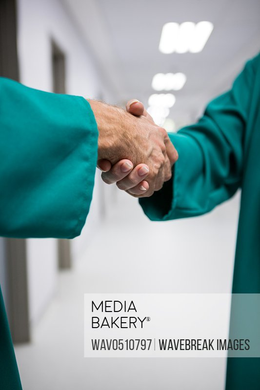 Mid section of surgeons shaking hands in corridor of hospital