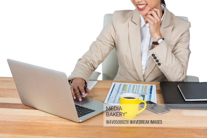 Mid-section of businesswoman working at her desk in office