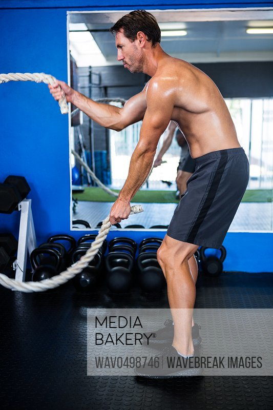 Shirtless athlete holding rope while exercising in gym