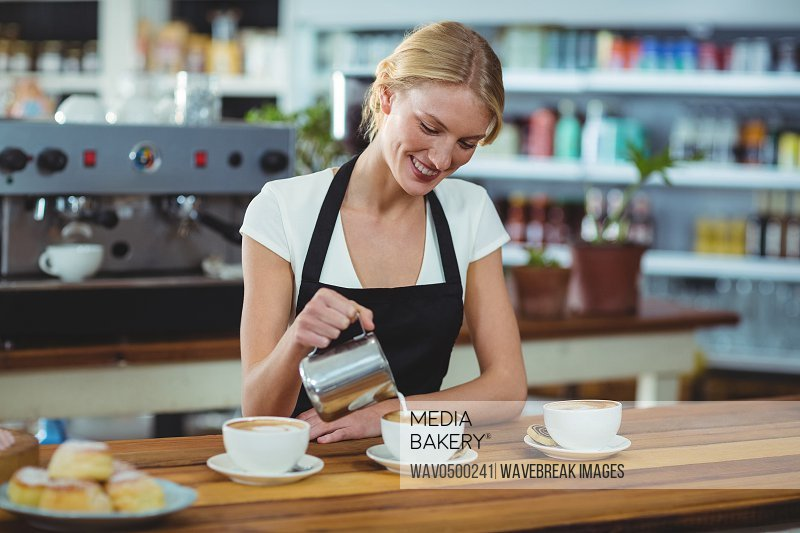 Smiling waitress making cup of coffee at counter in cafe