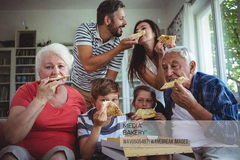 Multi-generation family having pizza together at home