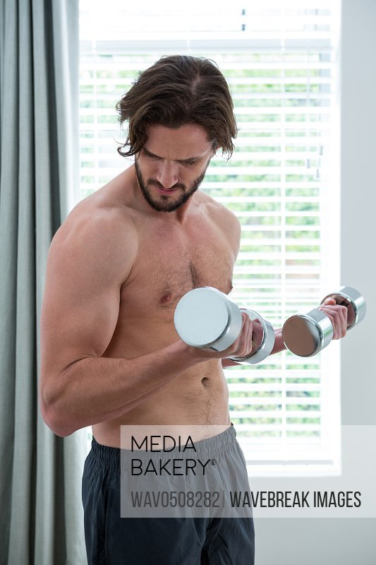 Man exercising with dumbbells at home