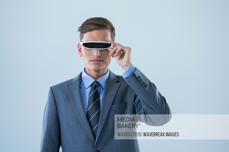 Businessman using virtual reality glasses against white background