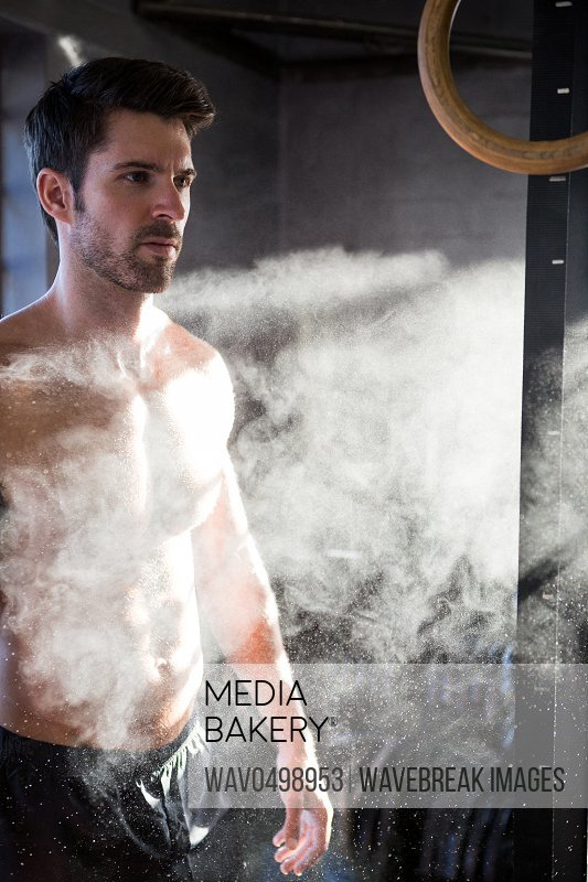 Shirtless young male athlete standing by chalk dust in gym