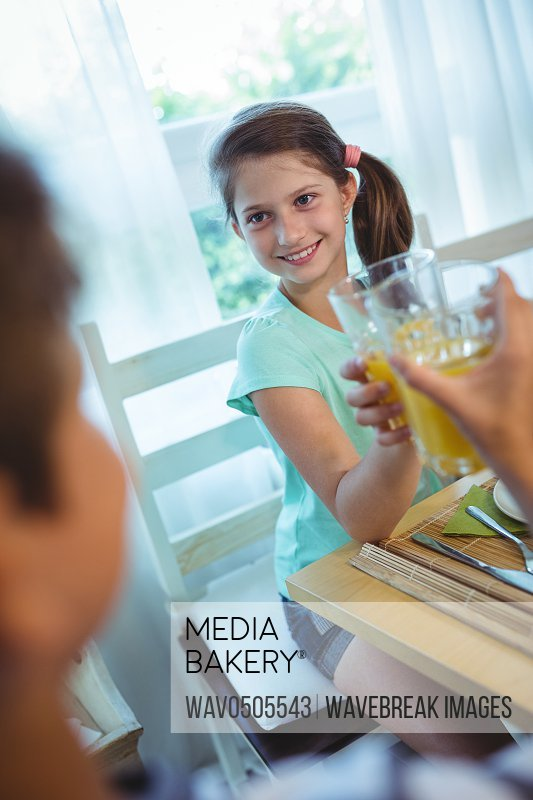 Smiling girl toasting glass of orange juice at dinning table