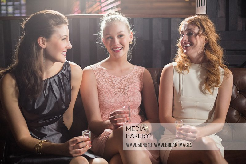 Portrait of smiling female friends holding shot glass of tequila in bar