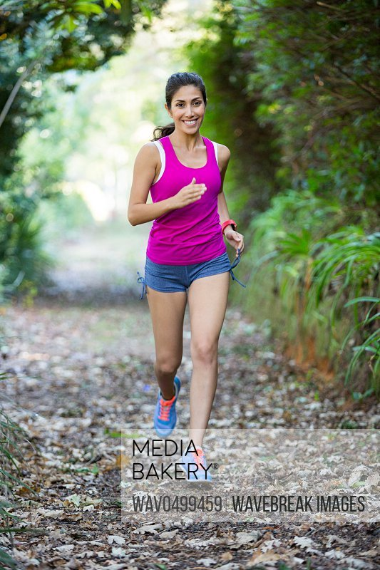 Woman jogging through a forest in the countryside