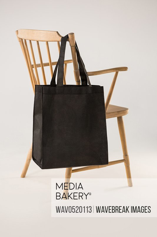 Black bag hanging on a wooden chair