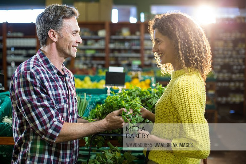 Happy couple buying vegetables in organic section of supermarket