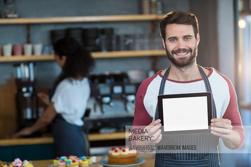 Portrait of smiling waiter showing digital tablet at counter in cafA?