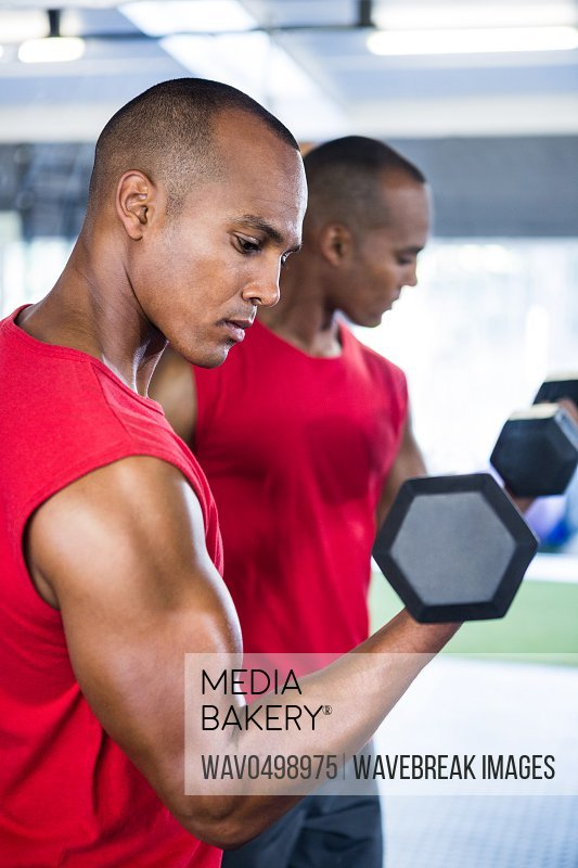Side view of man exercising with dumbbells against mirror in gym