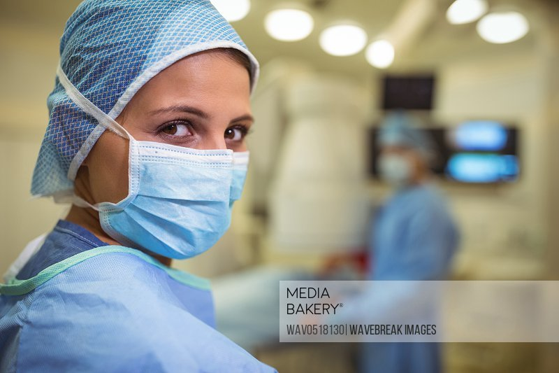 Portrait of female surgeon wearing surgical mask in operation theater
