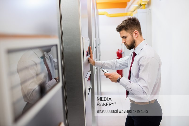 Technician using mobile phone in server room