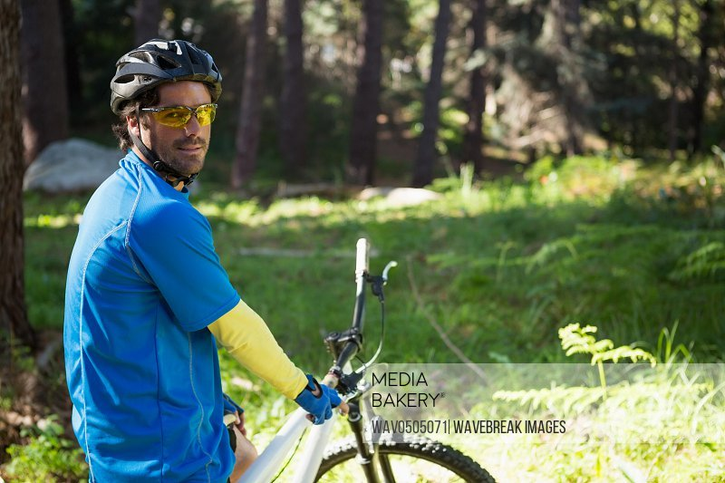 Portrait of male mountain biker with bicycle in the forest on a sunny day