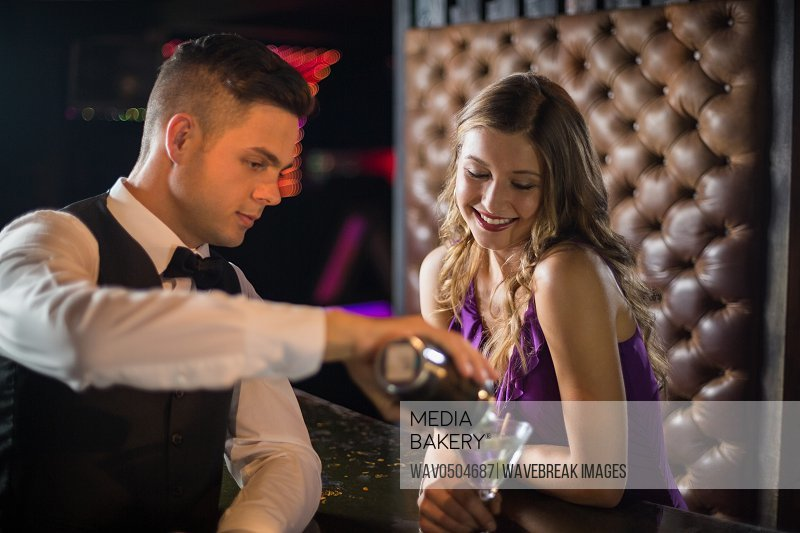 Smiling waiter pouring a cocktail in woman glass at bar counter in bar