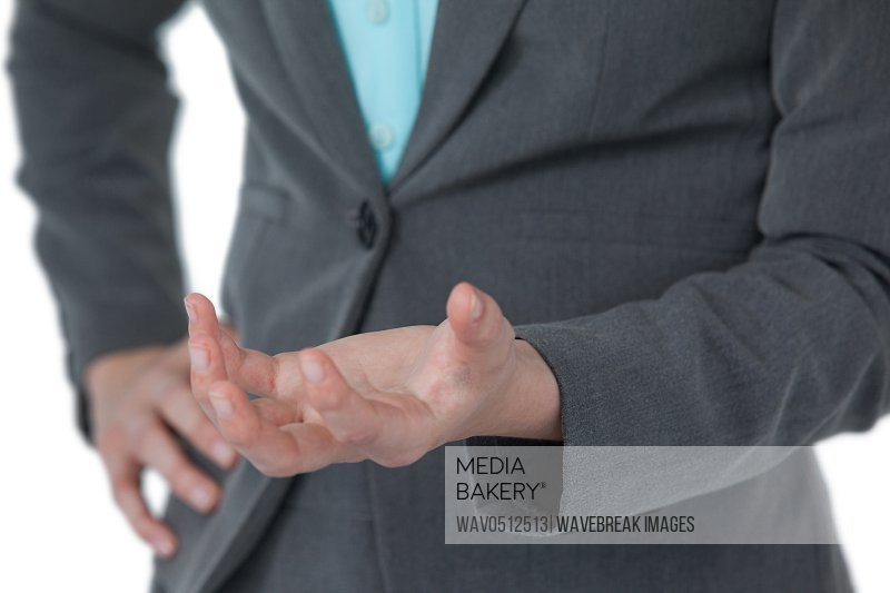 Mid section of businesswoman gesturing against white background