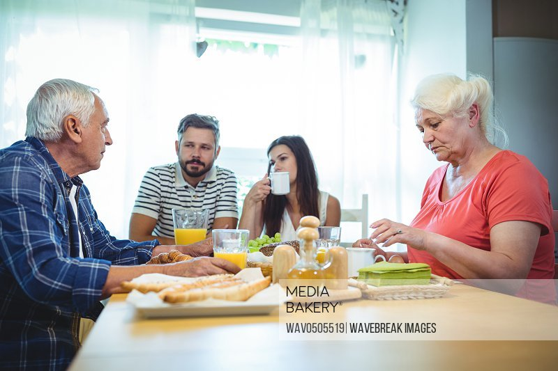Couple having breakfast with their parents at home