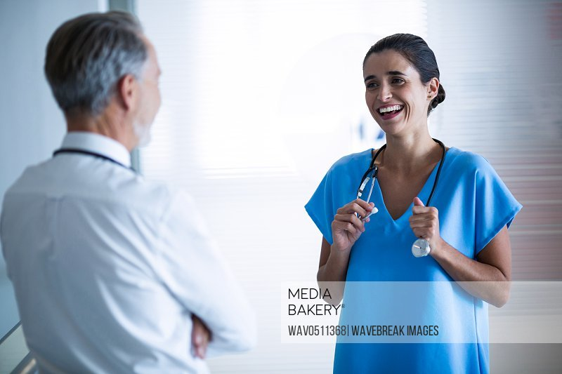 Doctor and colleague interacting with each other at hospital