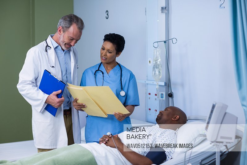 Doctor and nurse discussing report during visit in ward of hospital