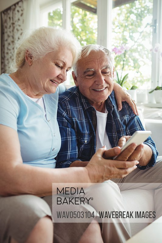 Senior couple using mobile phone at home