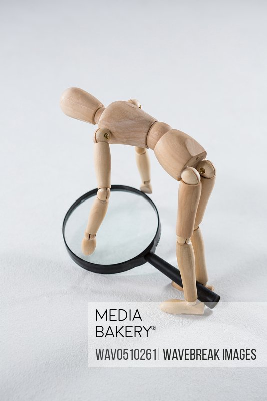Wooden figurine picking up a magnifying glass against white background