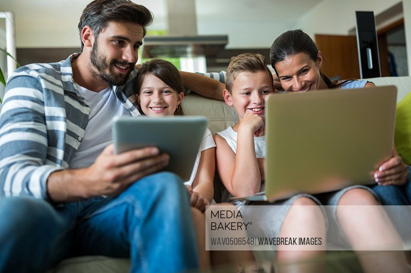 Happy family using laptop and digital tablet in the living room at home