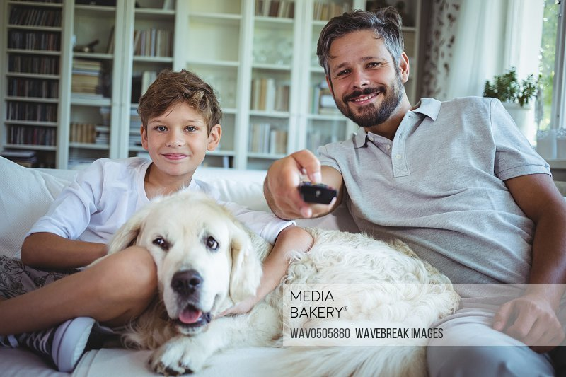 Father and son sitting on sofa with pet dog and watching television in living room at home