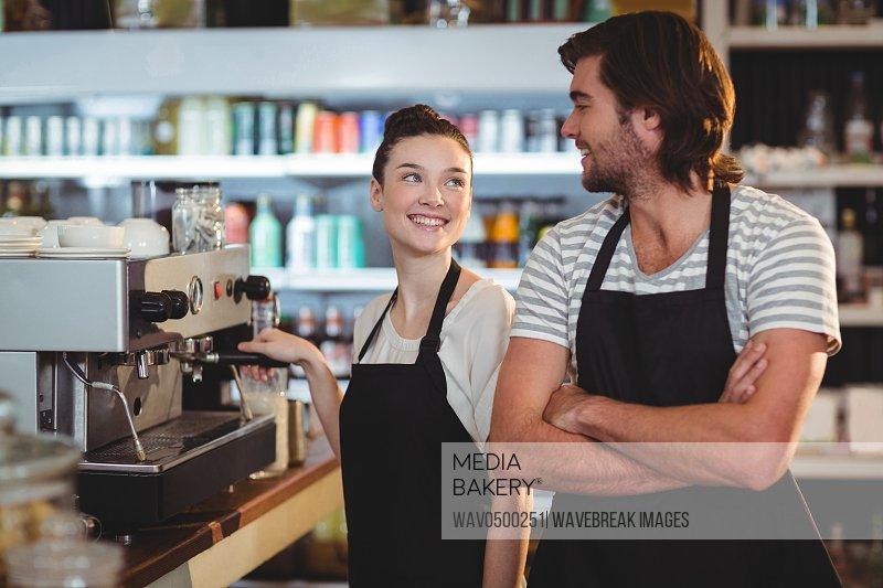 Waiter and waitress smiling at each other in cafe