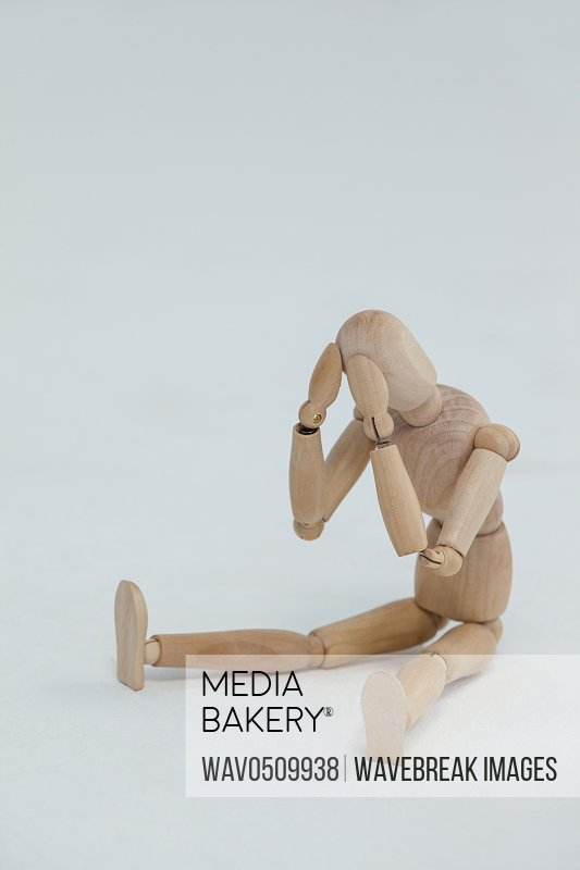 Tensed wooden figurine sitting with hands on head against white background
