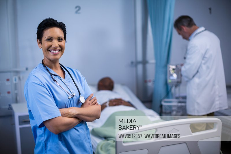 Portrait of female nurse standing with arms crossed in ward of hospital