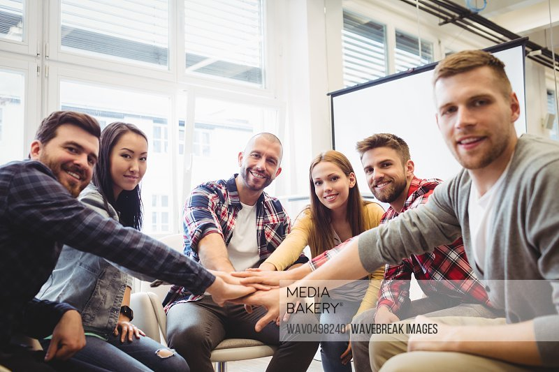 Portrait of smiling creative business people stacking hands in meeting room at office