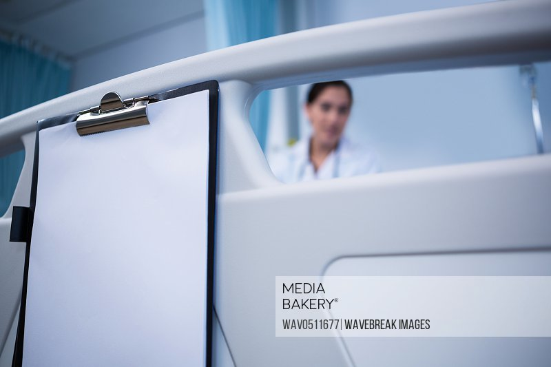 Close-up of clipboard hanging on bed in hospital