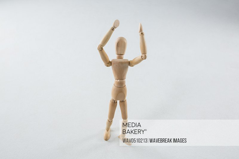 Wooden figurine standing with hand raised against white background