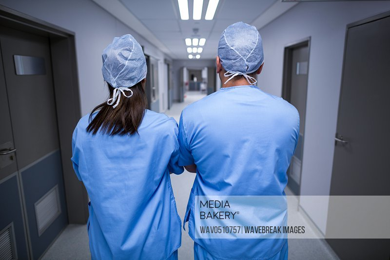Rear view of surgeons standing in hospital corridor