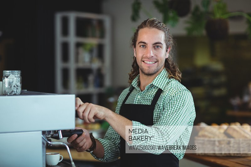 Portrait of smiling waiter making cup of coffee in cafe