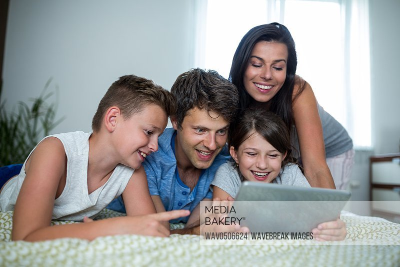 Happy family using digital tablet in bedroom at home