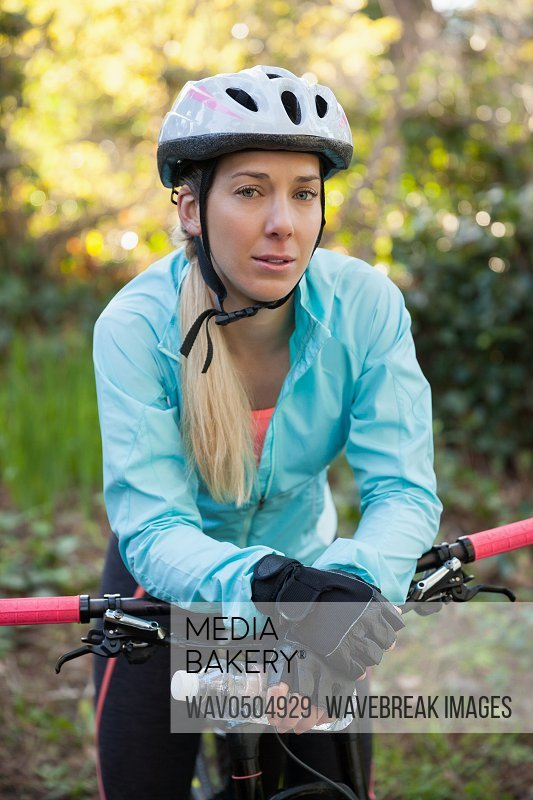 Portrait of female mountain biker standing with bicycle in the forest