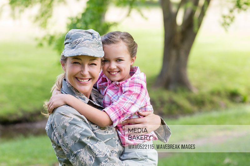 Portrait of happy female soldier with her daughter in park