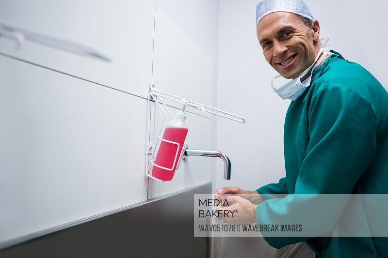 Portrait of surgeon washing hands in hospital
