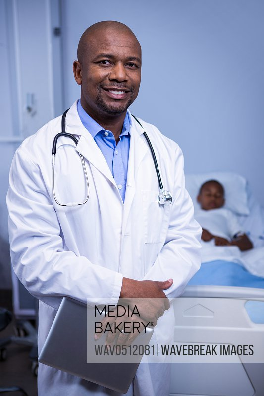 Portrait of smiling male doctor standing with digital tablet in ward at hospital