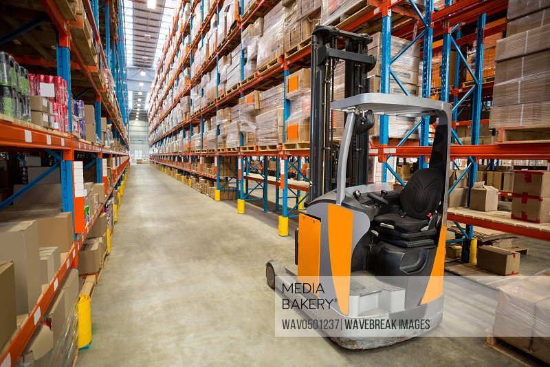Forklift and cardboxes in shelf at warehouse