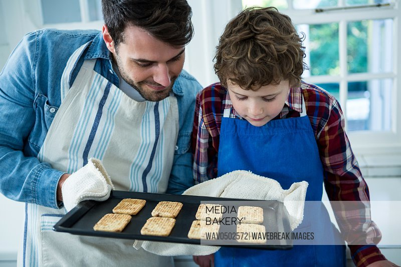 Father holding biscuits tray in the kitchen